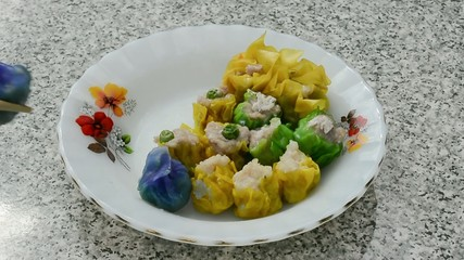 Colorful dim sum is put on a dish neatly with chopsticks
