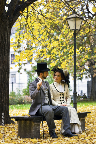 Old-fashioned dressed couple on a park bench in fall.