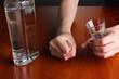 Drunk man drinks vodka at table close-up