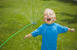 Young boy playing in the sprinklers outdoors