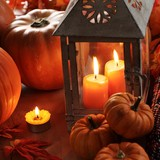 Lantern with burning candles and pumpkins
