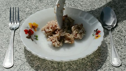 Three spoonful of steam brown rice are put on a dish.