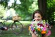 junge Frau mit Blumen im Park