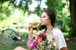 hübsche Frau mit Sekt und Blumen im Park