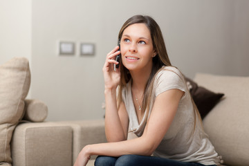 Woman using cellphone while sitting on couch at home