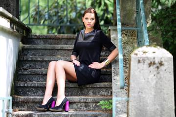 attraktives Model sitzt auf alter Treppe