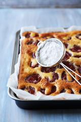 Homemade plum cake in a baking tin