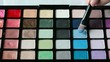 Woman is brushing eye shadow palette in closeup