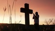 Silhouette of man praying under the cross at sunset/sunsrise