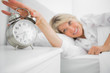 Blonde woman turning off alarm clock