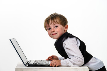 Freckled red-hair little boy with laptop.