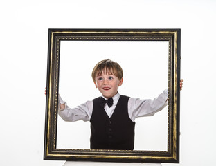 Freckled red-hair little boy with big picture frame.