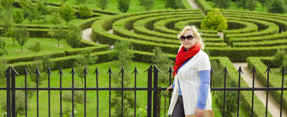 Smiling blond young woman against a garden labyrinth