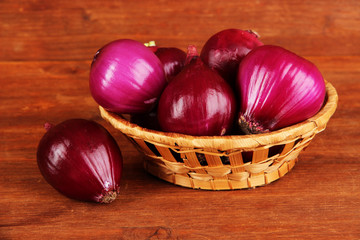 Purple onion in wicker basket on wooden background