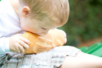 Three years old boy eating bread