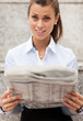 Brunette Businesswoman sitting on stairs with newspaper