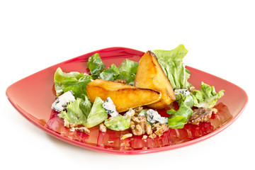 Salad with caramelised pears,walnuts and blue cheese, on red pla