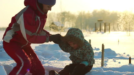 Young mother helps the child to get out of a snowdrift