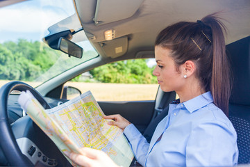 Woman is looking at a map inside her car