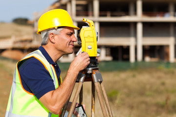 senior land surveyor working with theodolite