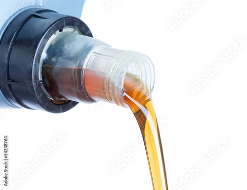 Engine oil pouring from a plastic canister. On a white backgroun