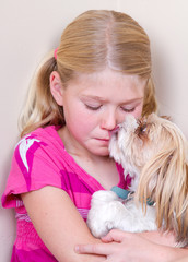 Dog licking childs face