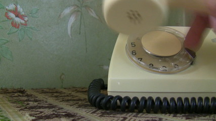 Woman hand dialing an old white telephone