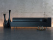 Black couch in front of illuminated concrete wall