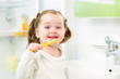 smiling kid girl brushing teeth in bathroom