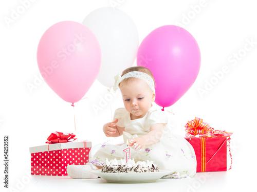 baby girl touching light on birthday cake