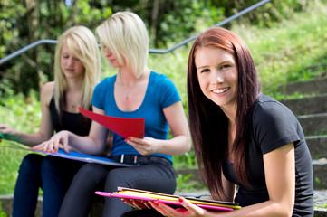 3 Schülerinnen auf Treppe im Freien beim lernen