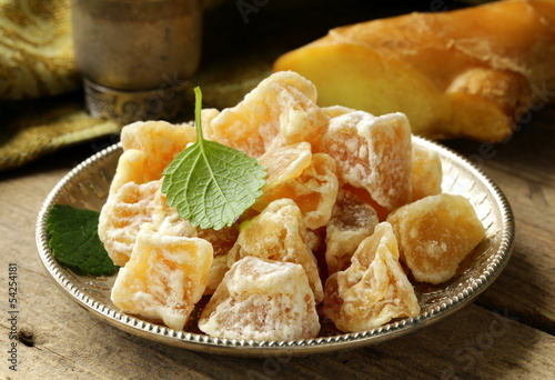 sugared ginger (candied) and fresh root on a wooden table