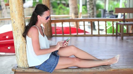 Young girl enjoys her phone on an exotic beach