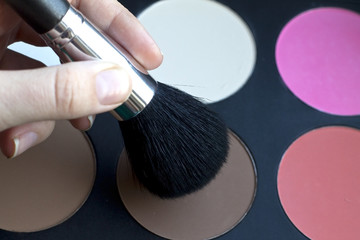The female hand holds a brush near a cosmetic palette