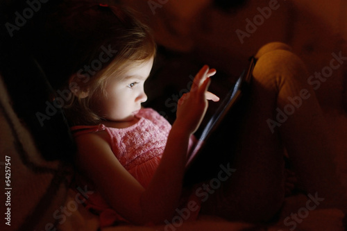 Adorable little girl playing on a tablet