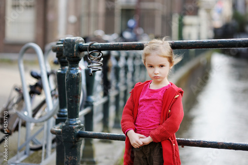Little girl standing by a row of bicycles