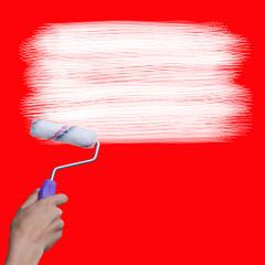 mano con pincel pintando en blanco en la pared roja