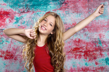 Blond happy kid girl in red happy with arms up