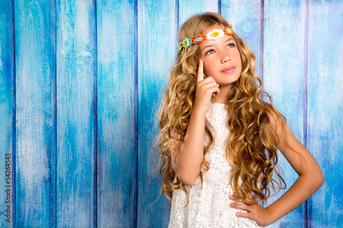 blond little girl thinking in vintage  wood background