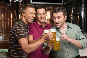 Old friends. Three happy friends drinking beer at the pub