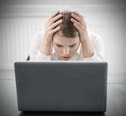Young  woman with computer worried about work done