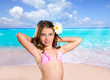 Brunette girl in tropical beach with daisy flower happy