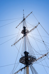 Mast of the sail boat on the blue sky background with sunlight