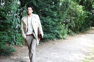 gehender Mann im Anzug mit Tasche