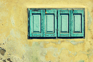 Yellow house facade with green shutters in Fira