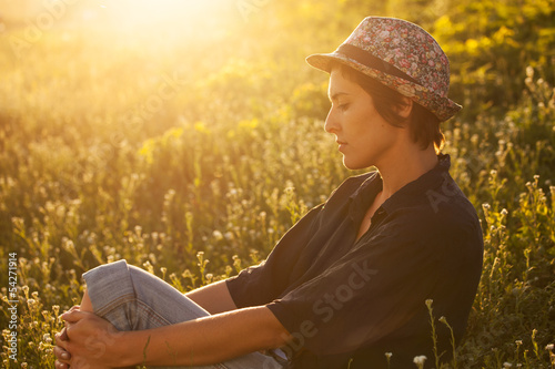 Cute girl sitting in the grass on a sunny evening