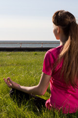 Young woman siiting on the grass in yoga pose