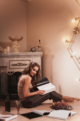 young woman sitting and reading magazine indoor shot