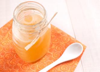 Jar with fresh honey on orange napkin