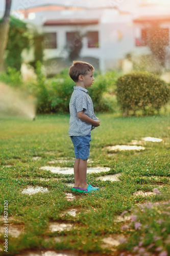 little boy walks in the park on the wet grass in a spray of wate
